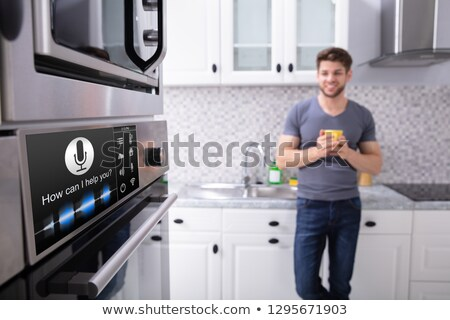 Man Looking At Oven With Voice Recognition Function Stock photo © AndreyPopov