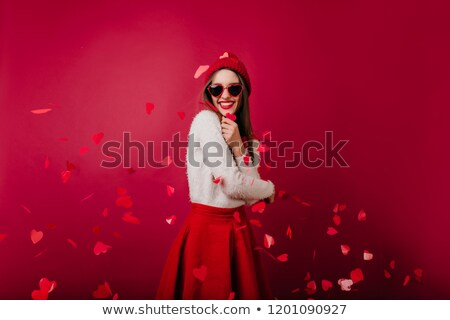 Portrait of a happy young woman celebrating under confetti shower Stock photo © deandrobot