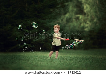 cute little boy is playing with big bubbles outdoor stock photo © galitskaya