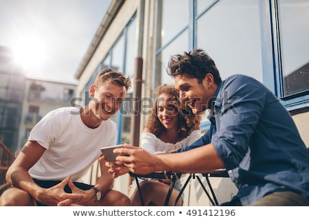 friends with smartphones hanging out in summer Stock photo © dolgachov
