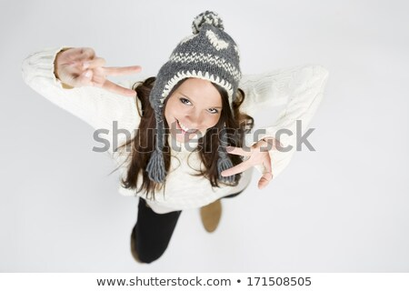 Cute girl in warm winter clothes making victory sign. Stock photo © lichtmeister