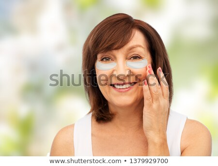 happy senior woman with hydrogel under-eye patches Stock photo © dolgachov