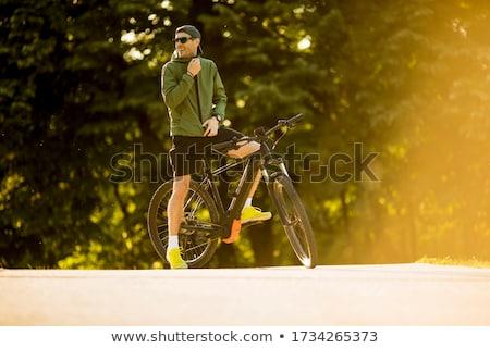 молодым человеком горных велосипедов электрических батареи красивый парка Сток-фото © boggy