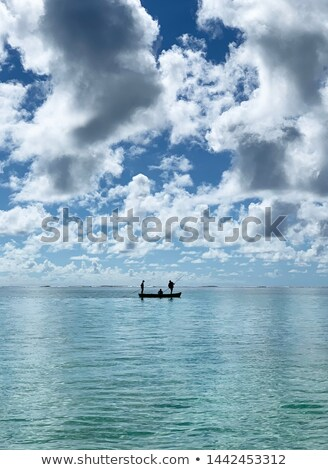 A small ship with people swimming in the sea under the sunset stock photo © Borissos