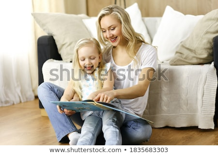family sitting on floor reading book at home stock photo © dacasdo