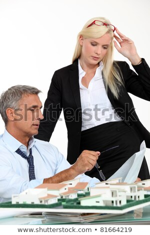 Stock photo: a boss and his female assistant thinking behind a subdivision model