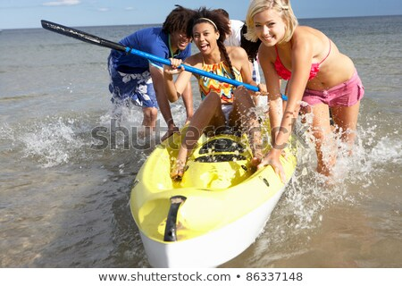 Teenage girls in sea with canoe Stock photo © monkey_business