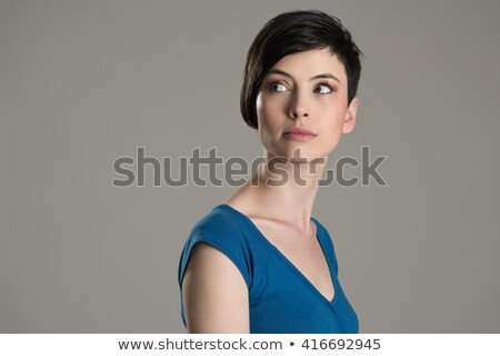 Portrait of a young pensive woman looking away on gray background Stock photo © deandrobot