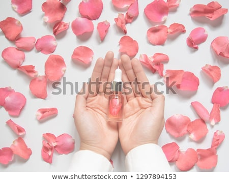 Pink rose in woman hand and bottle with essence oil on white bac Stock photo © tetkoren