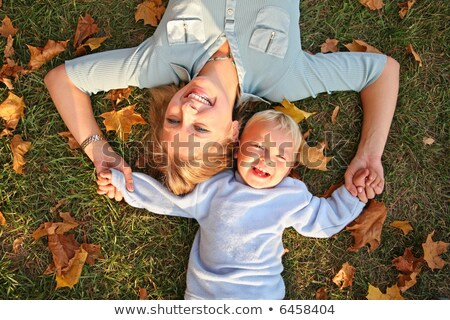 blue-eyed blond lies with the son on the earth at the park in autumn stock photo © Paha_L