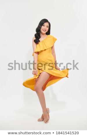portrait of a pretty young woman in yellow dress stock photo © deandrobot