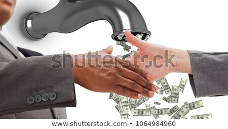 Close-up of business people shaking hands with money flowing from tap 商業照片 © wavebreak_media
