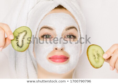 Girl holding kiwi slices over her eyes Stock photo © IS2