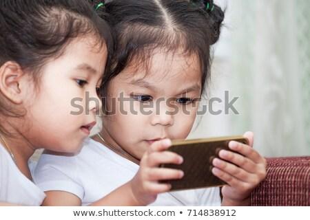 adorable girl playing on a digital tablet stock photo © vinnstock