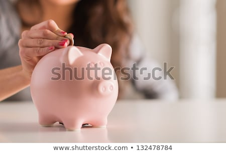Stock photo: Woman putting coin in to piggy bank