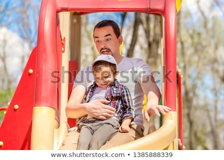 Family portrait on a slide in the park Stock photo © IS2