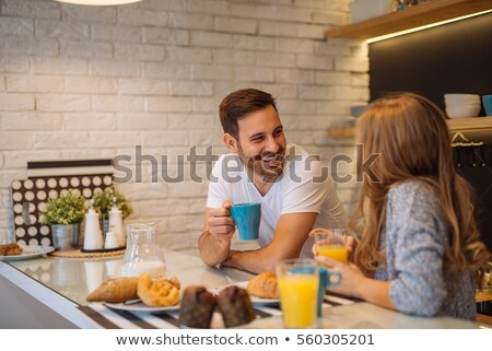 Young couple drinking orange juice at kitchen table Stock photo © IS2
