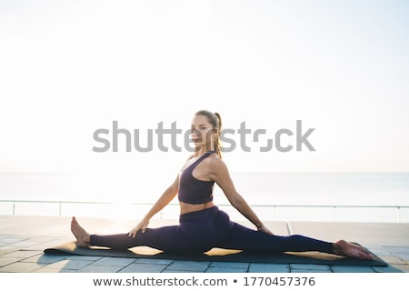 Calm young sportswoman at the seaside Stock photo © deandrobot