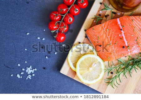 Fresh raw salmon slice on chopping board with oil tomatoes and lemon on stone kitchen table backgrou stock photo © DenisMArt