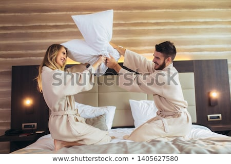 Playful young couple having pillow fight on bed Stock photo © boggy