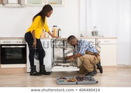 Woman Looking At Repairman Repairing Dishwasher In Kitchen Stock photo © AndreyPopov