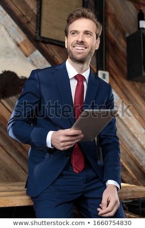 man sitting holds a book and looks to side stock photo © feedough