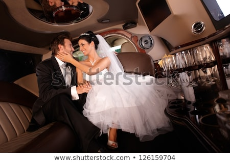 Handsome couple hugging in a luxury limousine Stock photo © konradbak