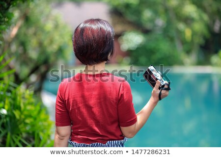 Enjoying vacation in China. Happy woman tourist with a Chinese flag and with traditional Chinese can stock photo © galitskaya
