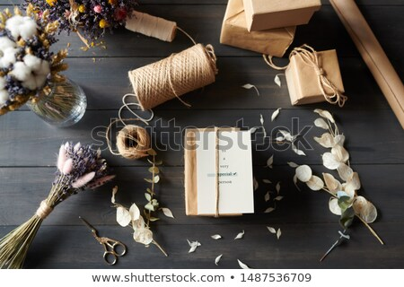 Above view of packaged gifts on table with messy petals Stock photo © pressmaster