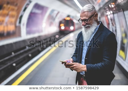 man using smartphone in a train station in berlin stock photo © nito
