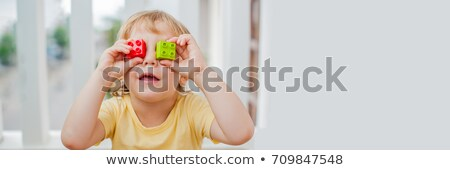 The boy makes eyes of colorful children's blocks. Cute little kid boy with glasses playing with lots Stock photo © galitskaya