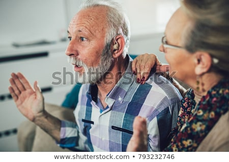 Two woman putting hearing aid into ear  Stock photo © vladacanon