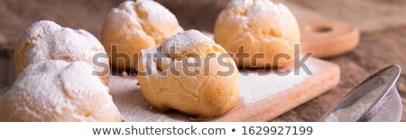Profiteroles with powdered sugar on wooden background. Rustic style. Close up. Stock photo © Illia