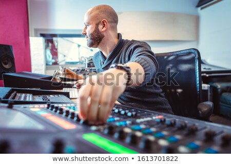 Sound engineer mixing a song in his studio Stock photo © Kzenon