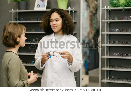 Pretty consultant in whitecoat showing new model of eyeglasses to client Stock photo © pressmaster