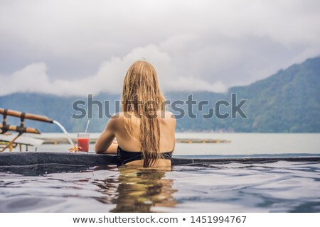 Geothermal spa. Woman relaxing in hot spring pool against the lake. hot springs concept Stock photo © galitskaya