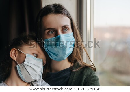 Stock photo: Mother with daughter child in mask looking from window, coronavirus.