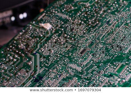 Technician or engineer is focused on repairing circuit board with soldering iron. Stock photo © Illia