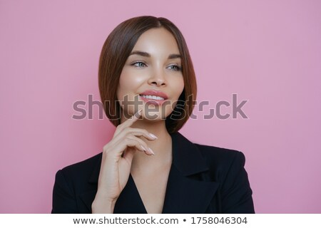 Portrait of satisfied lovely female employee looks away with dreamy cheerful expression, has manicur Stock photo © vkstudio
