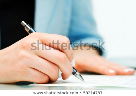Businesswoman lawyer signing contract documents writing on desk. Business woman working on paperwork Stock photo © Maridav
