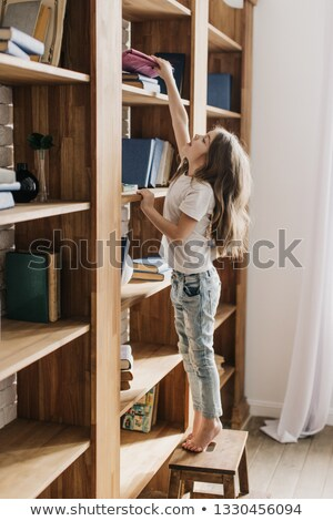 kid trying to reach a book in the library stock photo © zurijeta