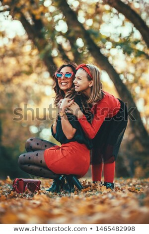 Woman crouching in woods looking at leaves Stock photo © photography33