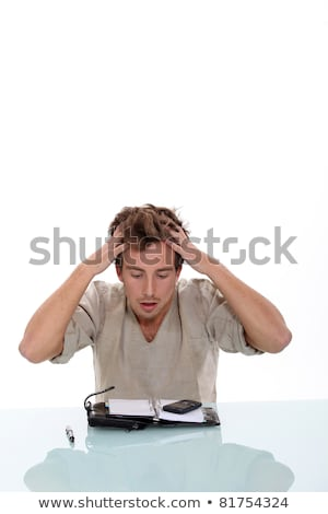 Young man tearing his hair out over the contents of his personal organizer Stock photo © photography33