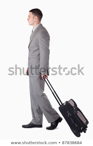 Portrait of a businessman with a suitcase walking against white babckground Stock photo © wavebreak_media