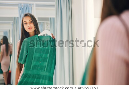 Woman standing in front of the mirror smiling while holding clothes  Stock photo © wavebreak_media