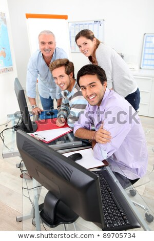 Four smiling people gathered round a computer in a classroom Stock photo © photography33