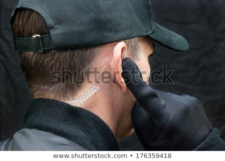 Security Guard Listens To Earpiece, Over Shoulder stock photo © jackethead