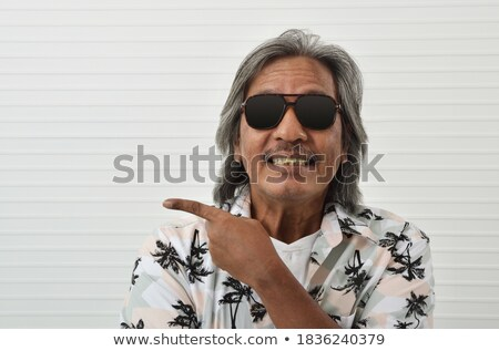 business man wearing sunglasses smiling and pointing up stock photo © feedough