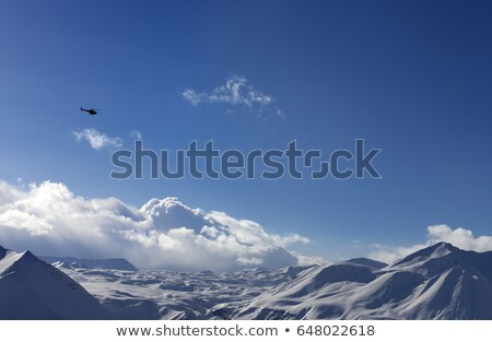 Stockfoto: Helicopter Above Snowy Plateau And Sunny Sky