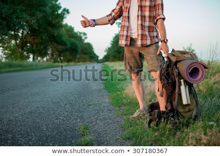 young smilimg caucasian tourist hitchhiking along a road stock photo © master1305